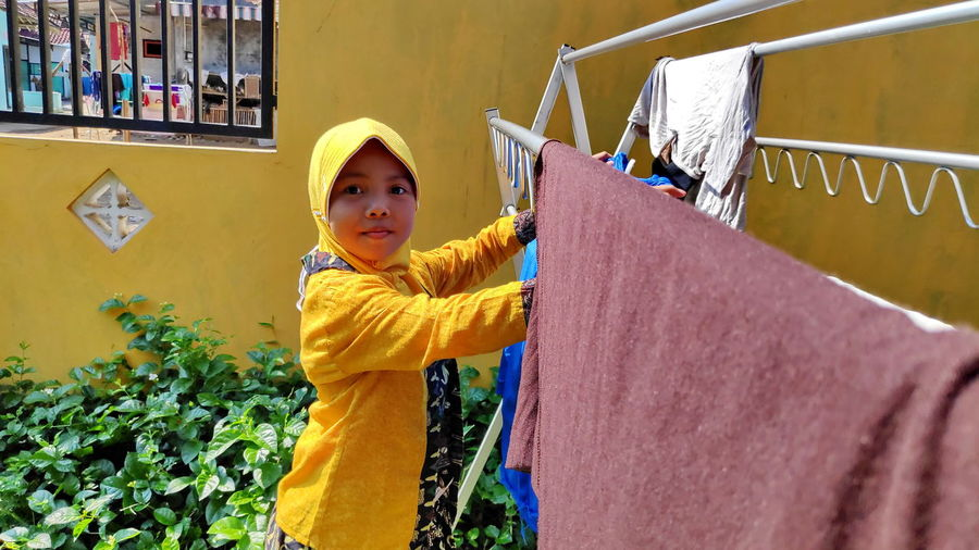 Portrait of girl drying clothes at yard