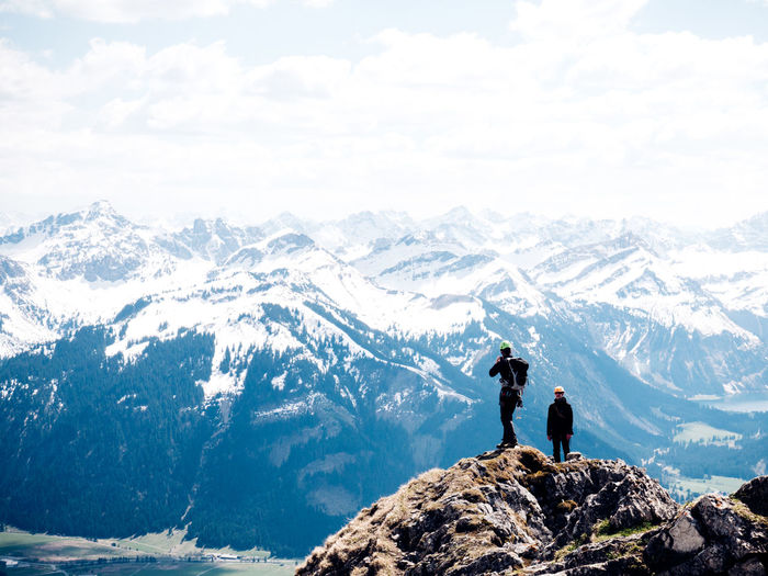 Two men on mountain against sky