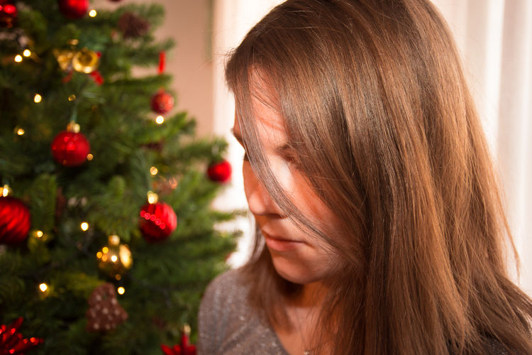Close-Up Of Young Woman By Christmas Tree