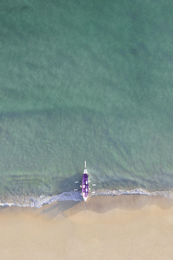 High angle view of a row boat lying on the shore