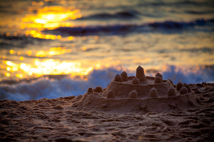 Sand castles on the beach with reflection of sunrise on the water. Beach Beauty In Nature Castle Castles Cloud - Sky Cold Temperature Day Landscape Morning Nature No People Ocean Outdoors Sand Scenics Sea Sun Sunrise Sunset Travel Destinations Vacations Water Wave