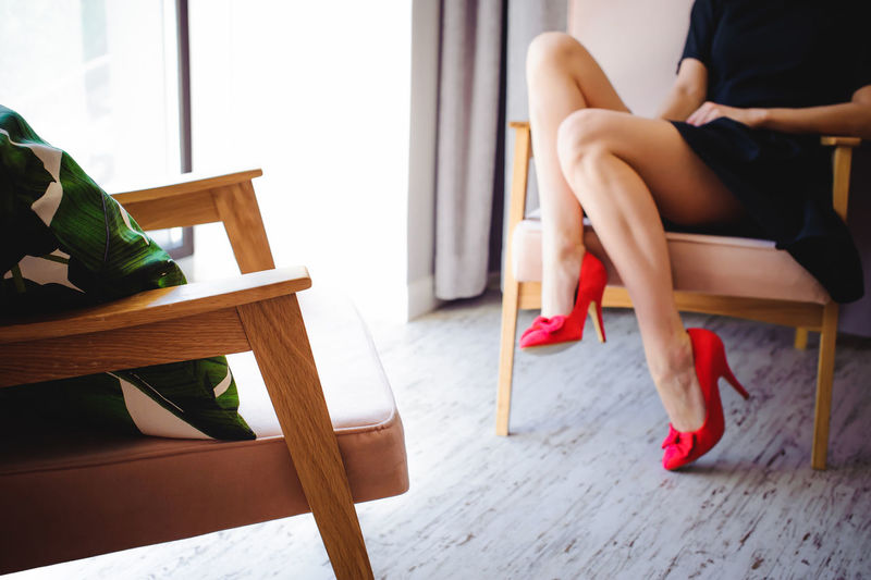 Low section of woman sitting on chair at home