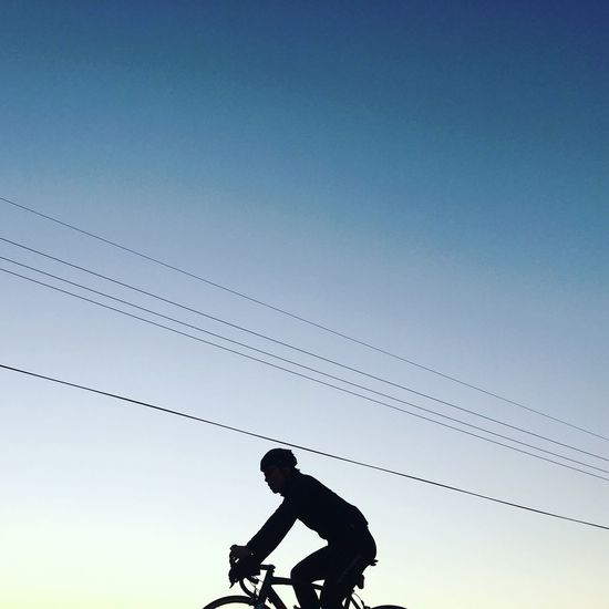 Silhouette man cycling against clear sky