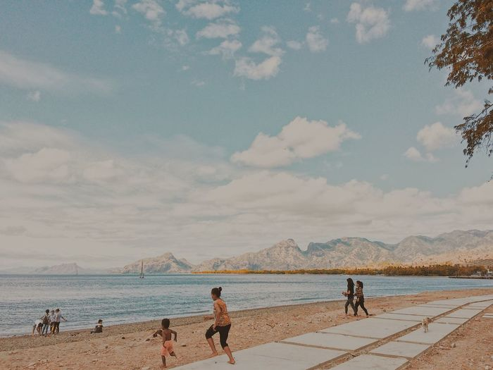 People on beach against cloudy sky