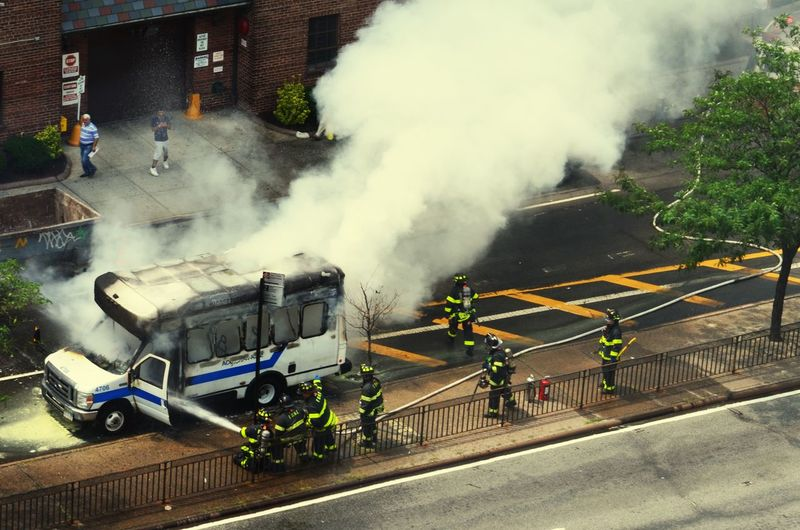 High angle view of firefighters putting out van fire on street
