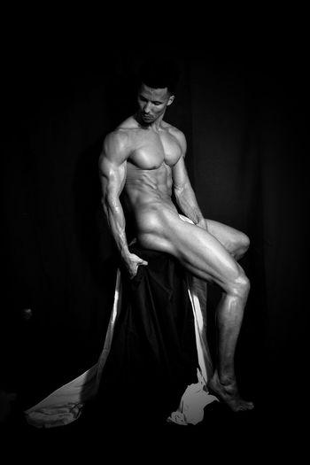 Naked muscular man sitting against black background