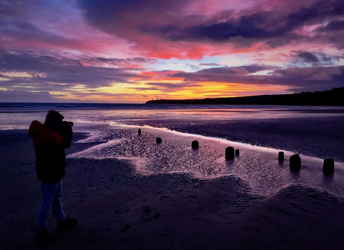 Shooting a winter sunset Waterford, Ireland Tramore Fiery Sunset... Fiery Sky Camera Coat Jeans Sand Wooden Stumps Tramore Beach Ripples In The Water Waves Water Boy Sunset Water Nature Real People Beauty In Nature Scenics Sky