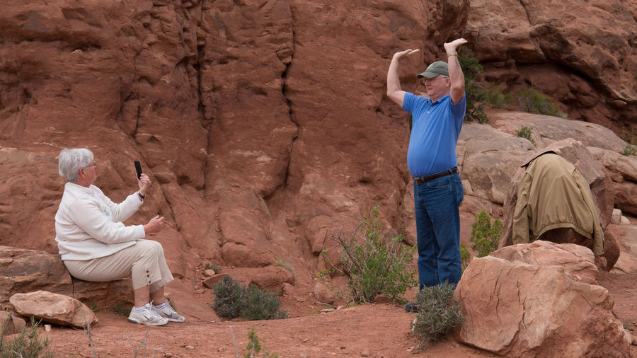 """""""Just a little bit higher!"""" Arms Arms Up Casual Clothing Desert EyeEm Best Shots Funny Landscape Old People Rock Rock Formation Seeing The Sights Shootermag Showcase: February Sitting Stone Taking Photos The Tourist Traveling USA Lost In The Landscape Connected By Travel"""