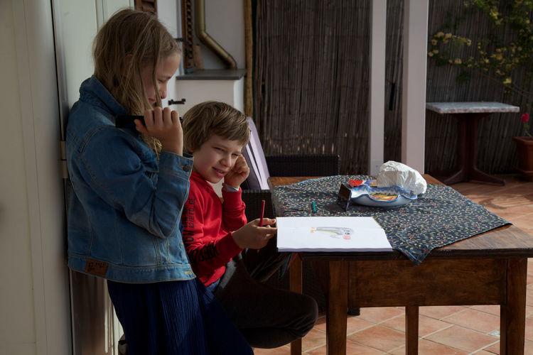 Siblings looking at drawing on table