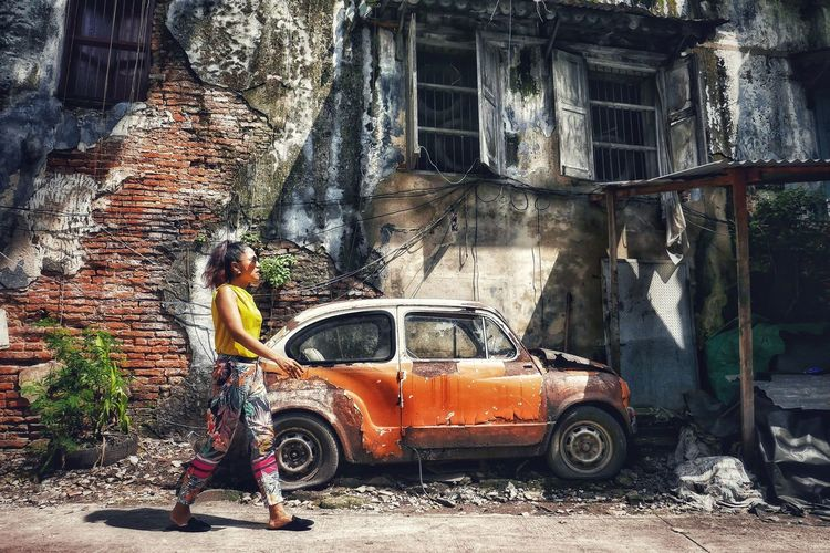 Side view of woman walking by old abandoned car and building