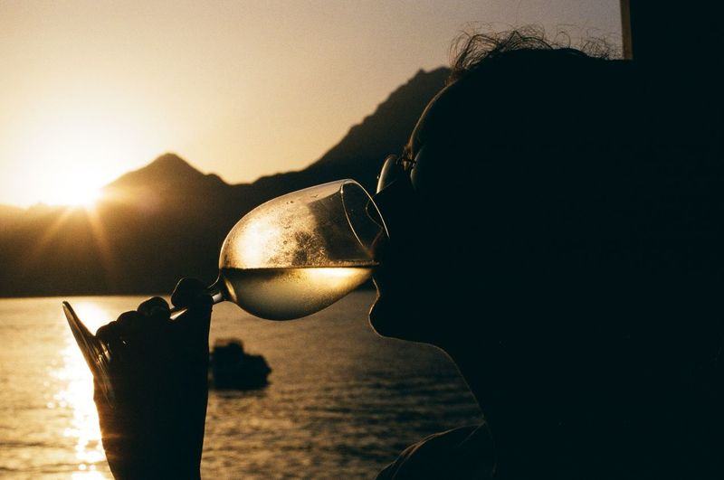 Close-up of silhouette woman drinking wine during sunset
