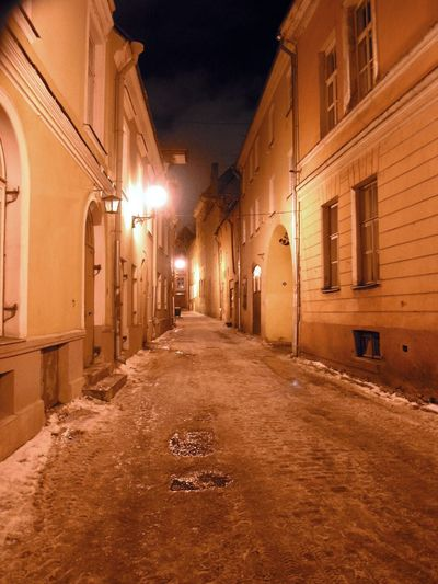 Empty alley along buildings at night