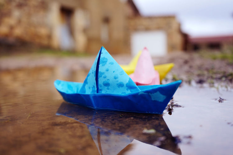 Close-up of multi colored paper boats floating on water