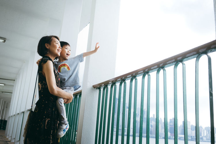 Mother carrying son while standing in corridor