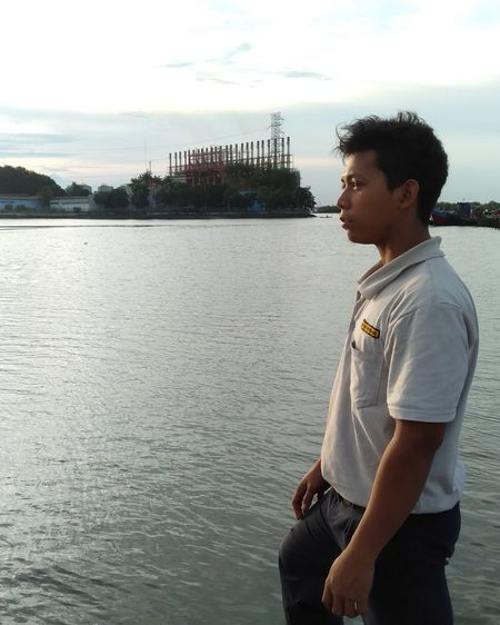 Side view of young man looking at lake against sky