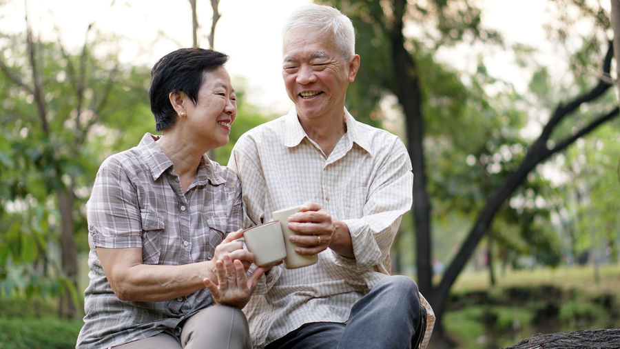 Smiling couple having drink while sitting in park