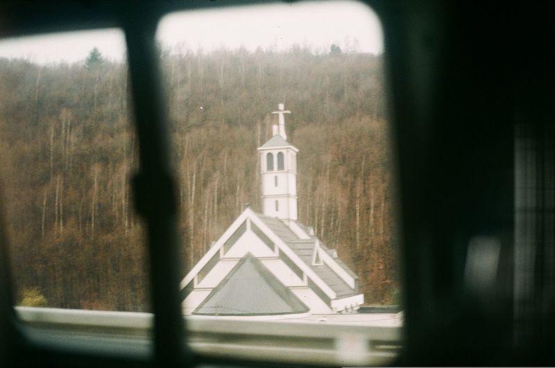 Clock tower amidst buildings against sky seen through window