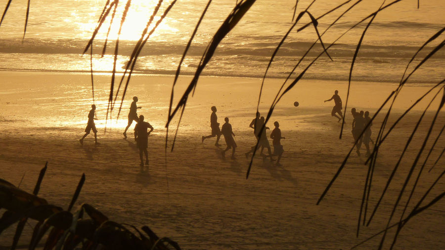 High Angle View Of People Playing Soccer On Beach During Sunset