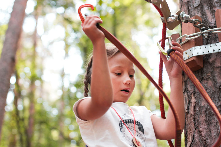 Low angle view of girl attaching safety harness on rope in forest