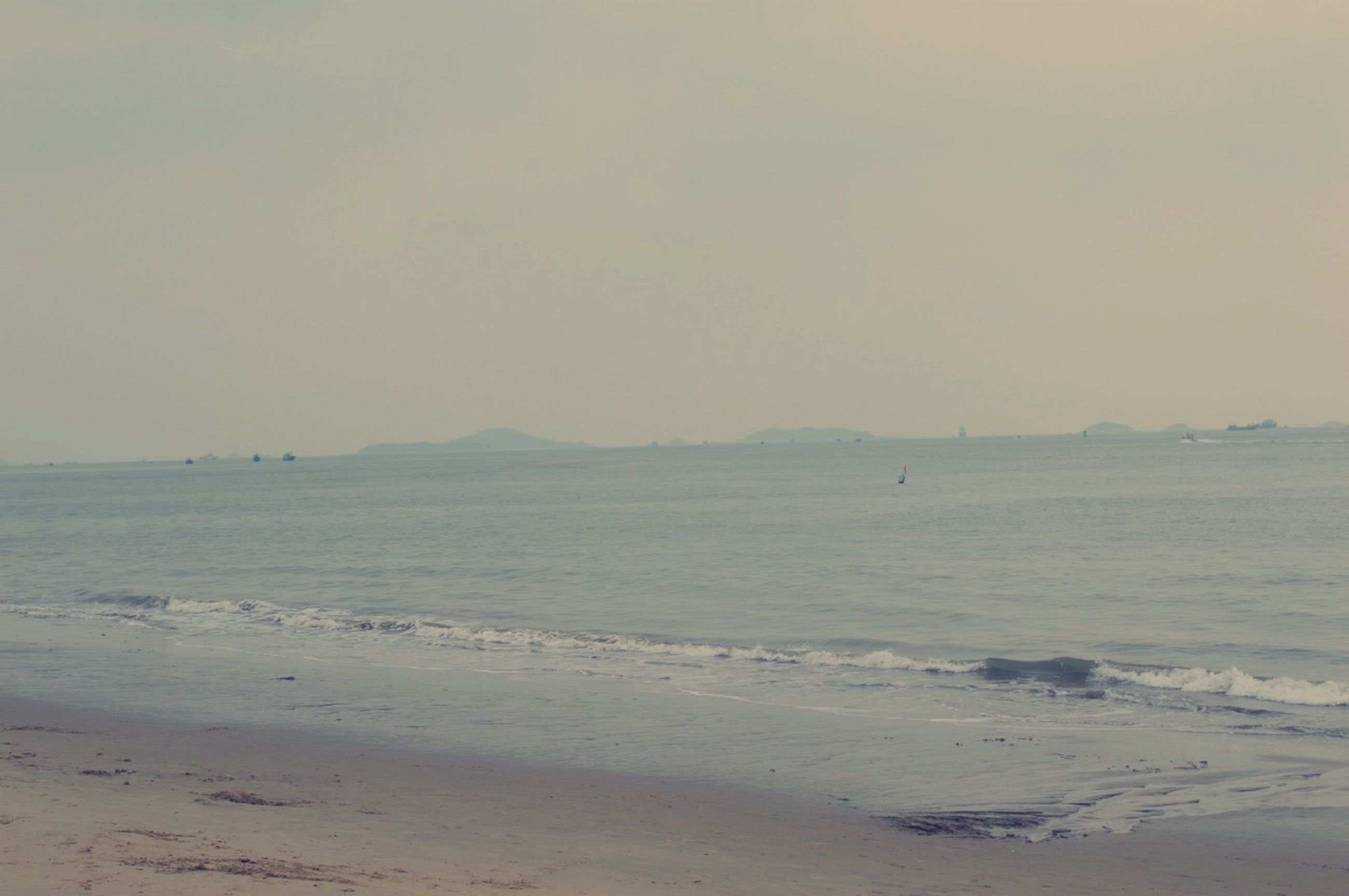 sea, water, beach, shore, tranquil scene, scenics, sand, tranquility, sky, beauty in nature, horizon over water, nature, wave, idyllic, coastline, nautical vessel, outdoors, remote, copy space, transportation