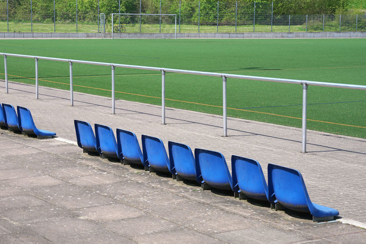 Blue seat row on a green Soccer field In A Row No People Absence Blue Empty Seat Day Sport Stadium Outdoors Soccer Football Fussball Amateur Elf Freunde Team Spirit Order Arrangement Friendship Symbol Fair Play The Winner Takes It All Championship Champions League