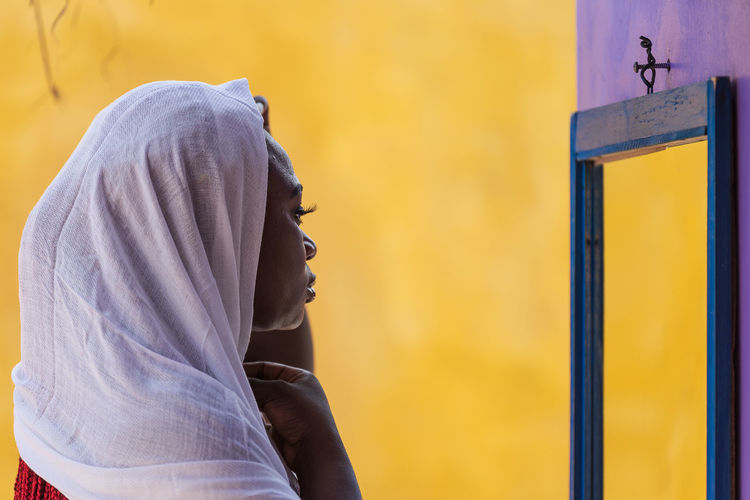 African ghana woman standing in front of a mirror with a white shawl covering her hair