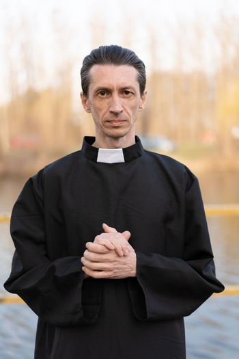 Handsome catholic priest portrait with collar Pastor Priest Collar Religion Religious  Belief Saint Father Beliver Man Men People person One Person Caucasian Middle Ages Catholicism Catholic Christianity Christian Faith Front View Waist Up Looking At Camera Portrait Focus On Foreground Standing Day Adult Clothing Serious Mature Adult Black Color Indoors  Occupation Mid Adult Courthouse