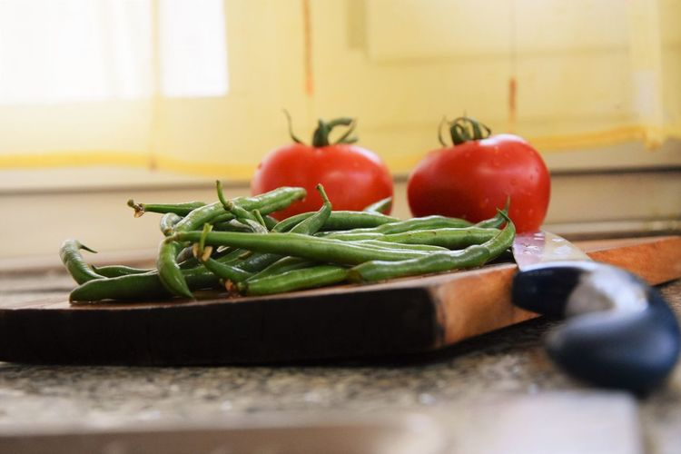 Green chilies and tomatoes on cutting board by knife in kitchen