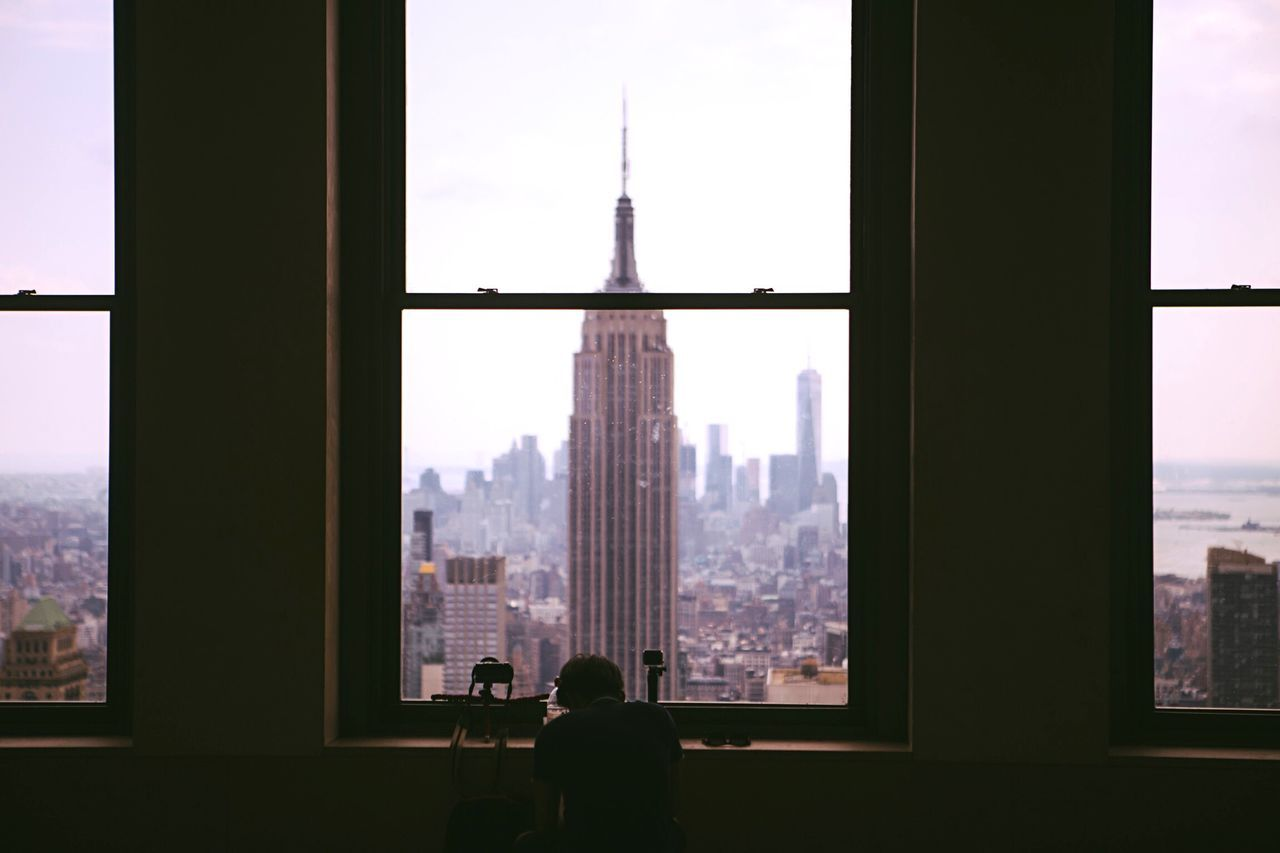 Person sitting on chair by window against empire state building