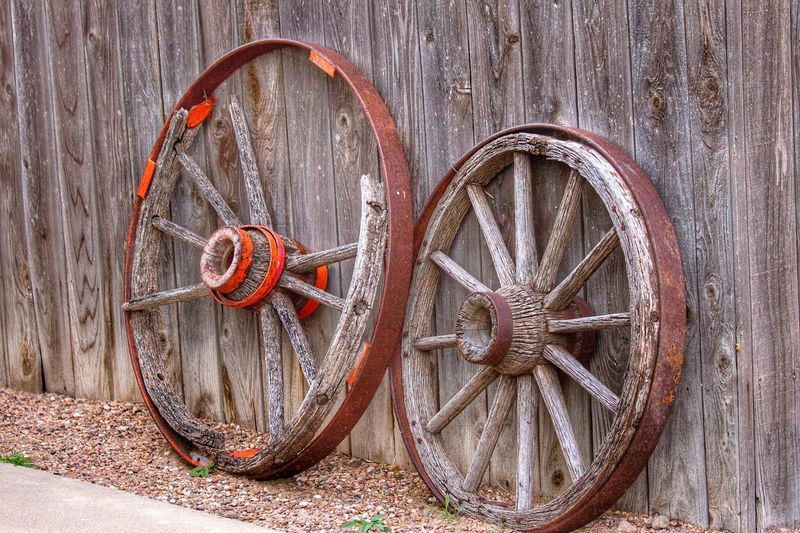 Old Wagon Wheels Pioneerlife Old Wagon Wheel Wood - Material Circle No People Geometric Shape Shape Transportation Day Design Pattern Outdoors Brown Wall - Building Feature Metal Close-up