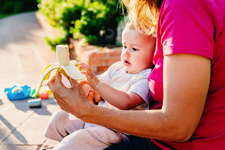 Midsection of mother feeding banana to baby at back yard