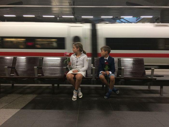 Full length of woman sitting at subway station