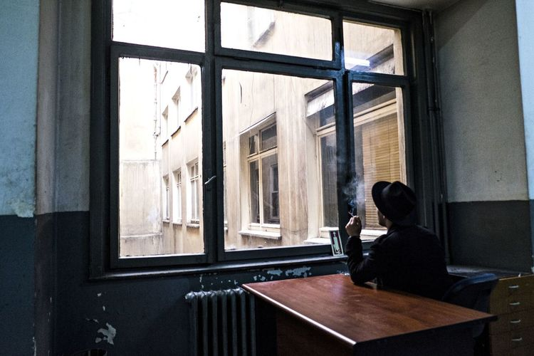 Rear View Of Man Smoking While Sitting On Table By Window