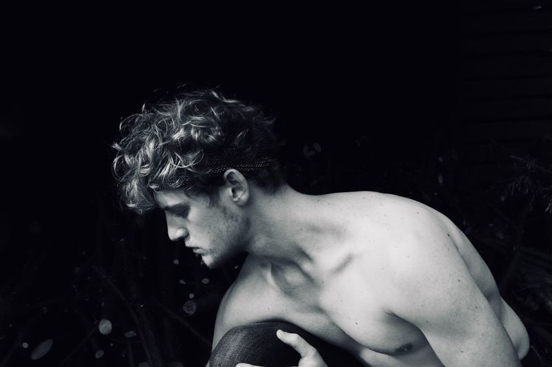 Shirtless Muscular Man Against Black Background