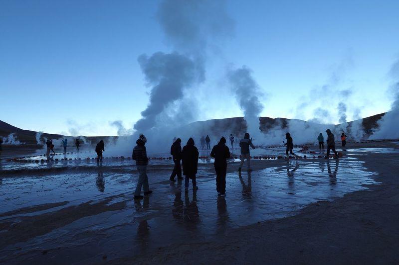 People at geyser against sky