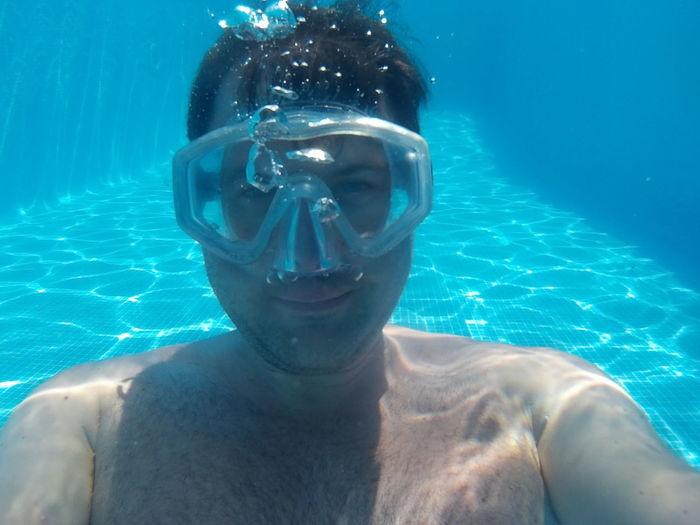 Portrait of shirtless man wearing scuba mask under swimming pool