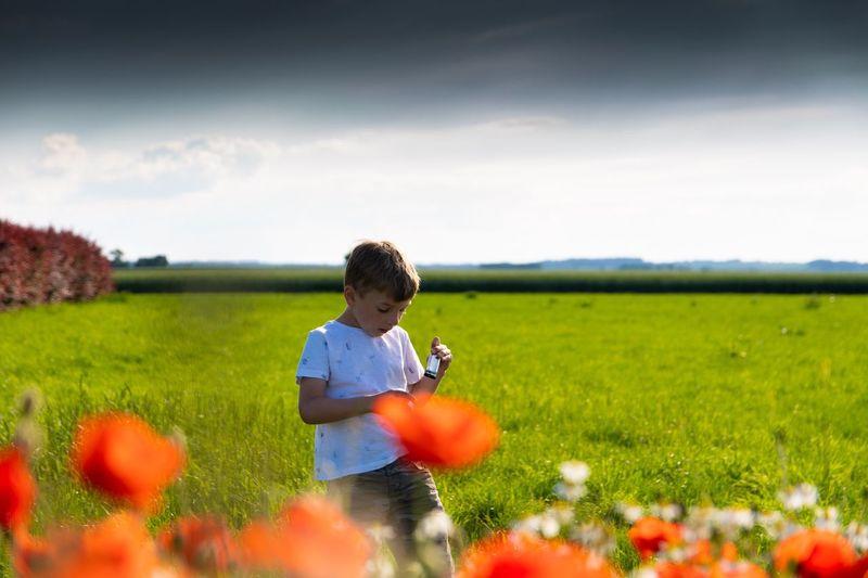 Rear view of boy on grassy field against sky