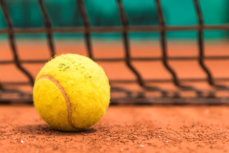 Close-up of yellow ball on tennis court