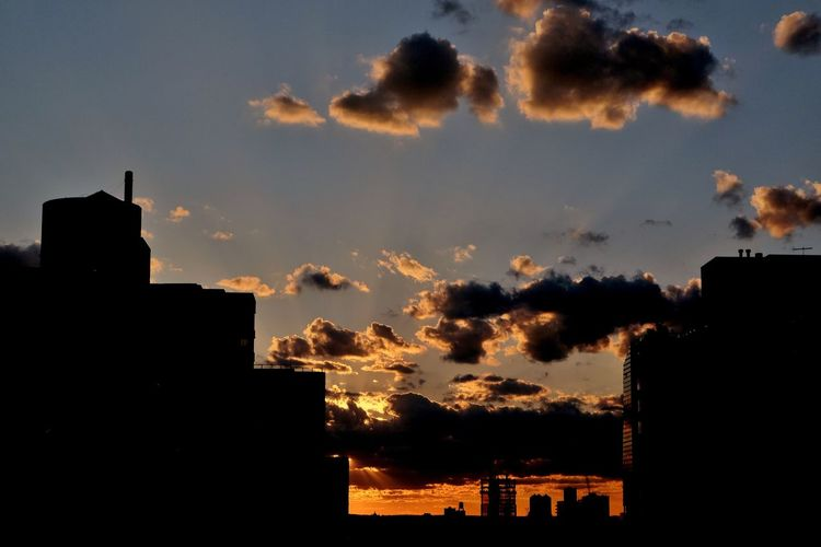 High section of silhouette buildings against cloudy sky