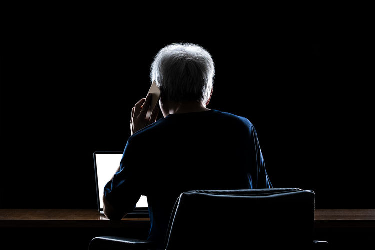 Rear view of person using mobile phone and laptop against black background