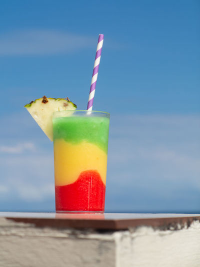 Multicolored cocktail on table with Blue Sky behind Drinking Straw Glass Cocktail Caribbean Sky Blue Relaxing Sea Holiday Vacation Red Yellow Green Blue Sky Pineapple Alchohol