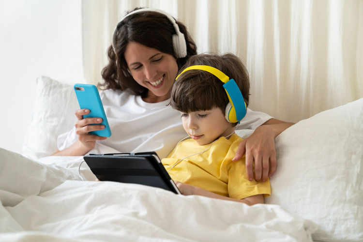 Happy woman using mobile phone while sitting on bed