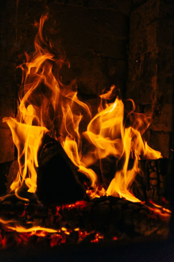 Close-up of fireplace with burning logs of wood. Burning Fire Flame Fire - Natural Phenomenon Heat - Temperature Motion Orange Color Log Wood Glowing Firewood Wood - Material Nature Night No People Close-up Fireplace Long Exposure Bonfire Blurred Motion Campfire
