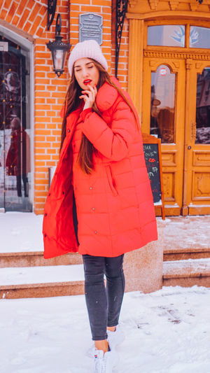 Beautiful happy smiling woman on the street in warm red winter coat on Christmas time on snowing. Winter Cold Temperature Warm Clothing Snowing Smiling Christmas Wintertime Woman Power women around the world EyeEm Best Shots EyeEm Colorful! Fashion Stories Red Lipstick Clothing Snow Standing One Person Young Adult Leisure Activity Real People Women Young Women Architecture Front View Scarf Full Length Outdoors