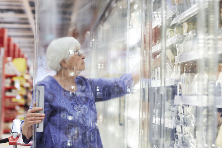 Woman looking through window at store
