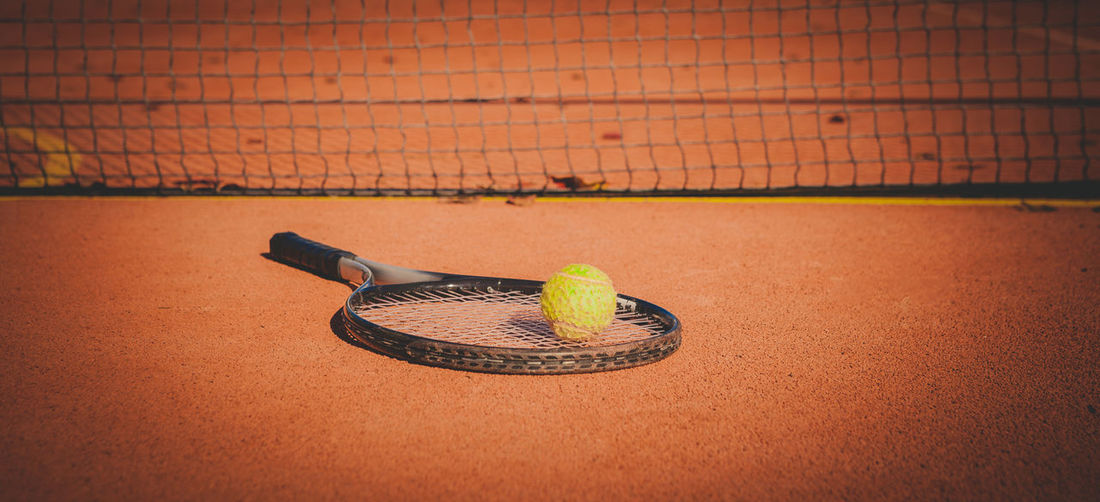 Close-up of tennis ball and racket on court