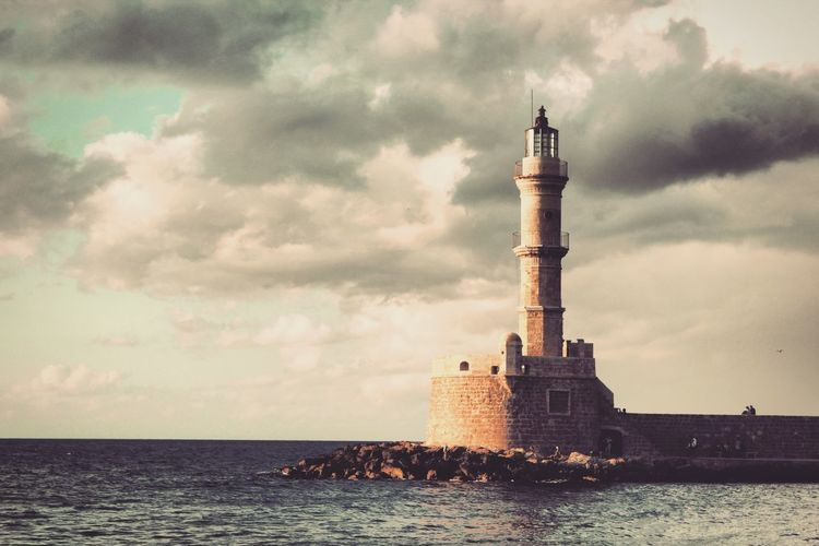 View of lighthouse by sea against cloudy sky