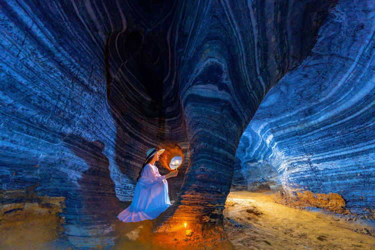 Full length of woman in illuminated cave