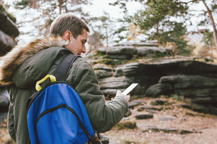 Rear view of man using smart phone while standing in forest