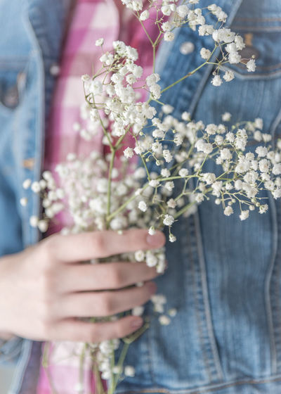 Girl holding delicate baby's breath flowers against her chest Beautiful Feminine  Pink Romantic Soft Baby's Breath Background Beauty Blue Bouquet Close-up Denim Jacket Female Feminity Flowers Girl Girl's Hand Human Hand Midsection One Person People Pretty Soft Colors  Whimsical White Flowers